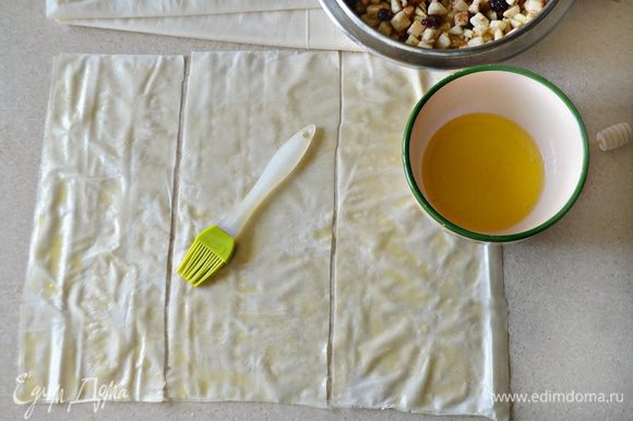 Тесто фило разморозьте при комнатной температуре. Аккуратно отделите листы друг от друга, смажьте лист растопленным сливочным маслом, сверху уложите еще один пласт и также смажьте маслом. Разрежьте сложенные листы теста на 3 части. Также проделайте и с другими листами фило.