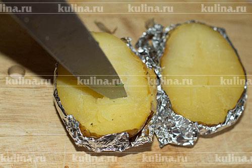 Достать картофель из духовки, разрезать пополам.