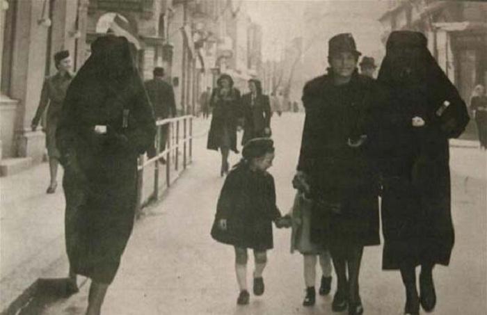Мусульманка прикрывает желтую звезду своей еврейской соседки вуалью, чтобы ее никто не увидел.