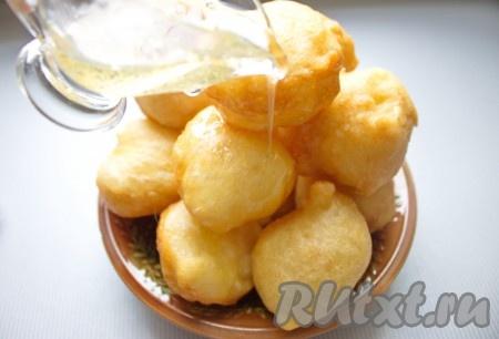 """Готовые греческие пончики """"Лукумадес"""" выложить на блюдо и полить горячим медовым сиропом. Часть сиропа можно оставить для подачи."""