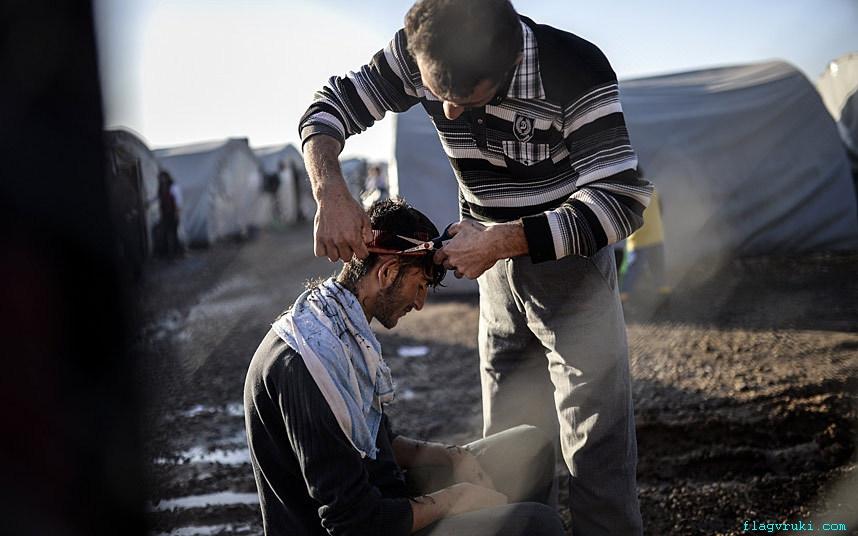 Сирийский курд организовал импровизированную парикмахерскую в лагере беженцев Роджава в Шанлыурфе, Турция.