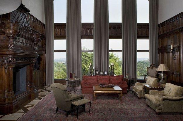 Стены облицованы панелями из темной древесины, на окнах – тяжелый, монументальный текстиль
