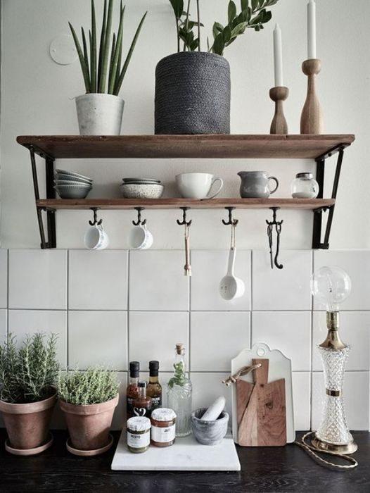 Стильно и удобно разместить чашки и прочие мелочи можно с помощью крючков под навесными полками.