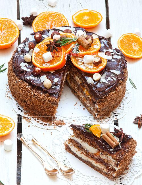 Украсьте торт мандаринами, орехами, пряностями, травками и кокосовыми кранчами. Уберите торт в холодильник до подачи. Разрежьте торт на порционные куски и подайте к столу.
