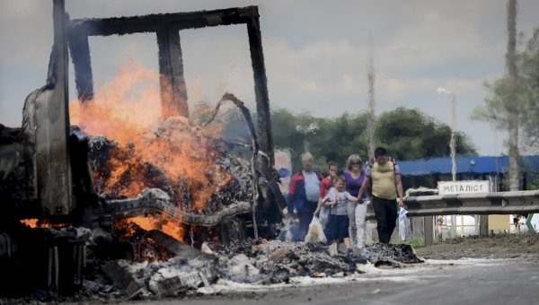 Беженцы у горящего грузовика на окраине Луганска после артиллерийского обстрела поселка Металлист