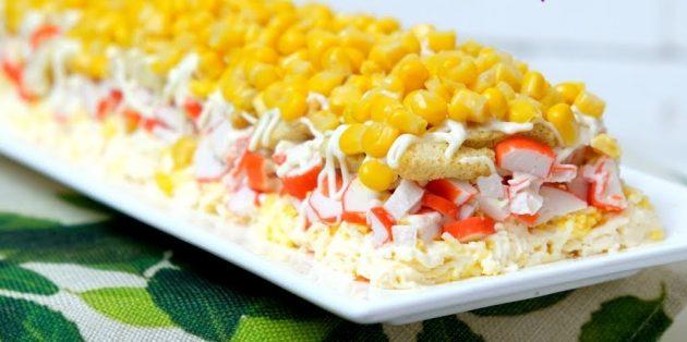 Слоёный салат с сухариками, крабовыми палочками, кукурузой и плавленым сыром