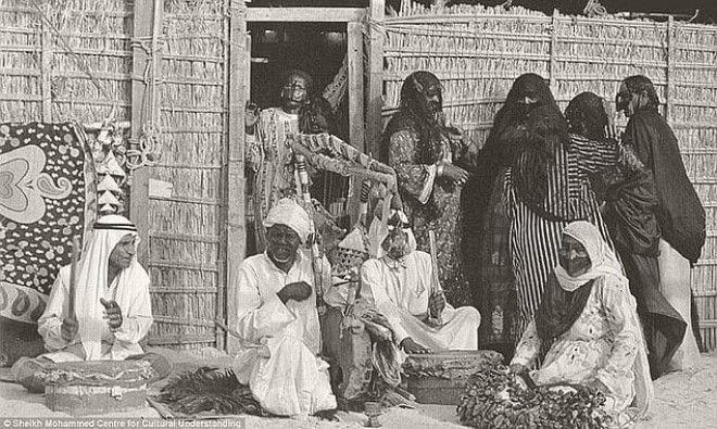 Бедуины играют музыку около дома, 1960-е. Иногда они приходили в Дубай и занимали там простые хижины из пальмовых деревьев