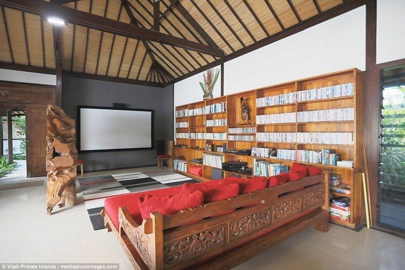 Гостиная в хозяйской резиденции с большим диваном, книжными полками и огромным телевизором ynews, остров, продается, продается остров, рай, райское место, тихий океан, тропический курорт