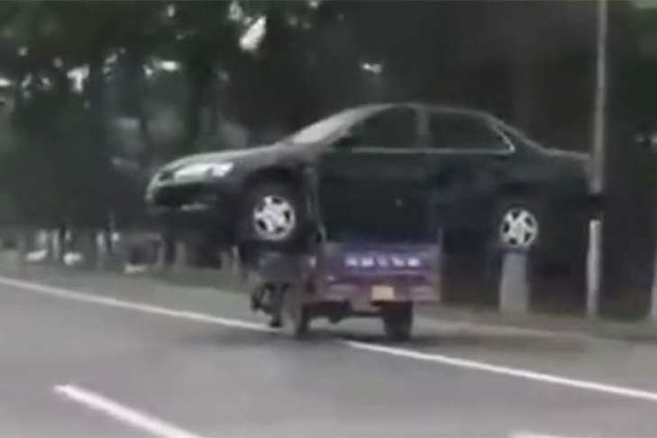 Китаец умудрился перевезти автомобиль на мотоцикле