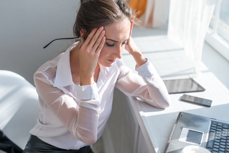 Portrait of tired young business woman suffering from headache in front of laptop at office desk.
