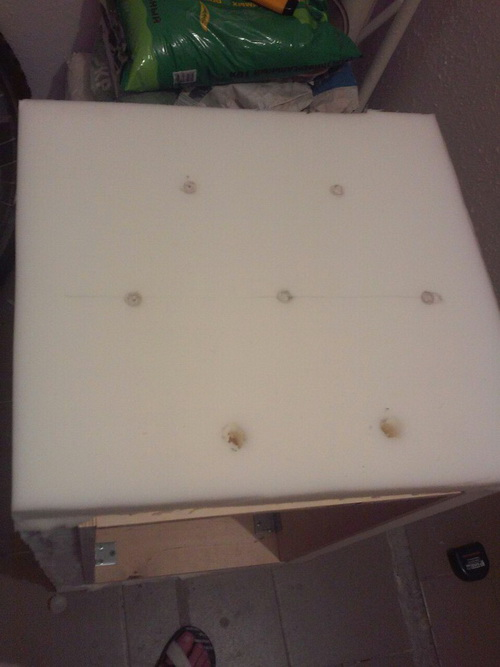 На внешние стенки пуфика приклеиваем поролон. В нем наносим разметку под коретную стяжку и вырезаем отверстия под пуговки