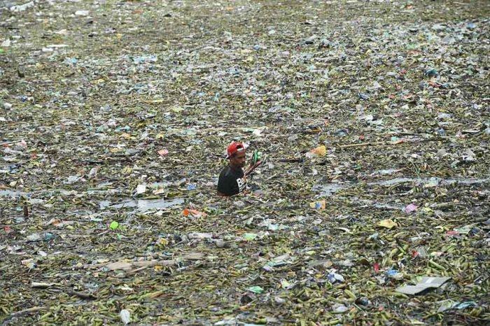 Человек собирает перерабатываемые материалы среди плавающего мусора после тропического шторма Нида.