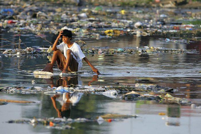 Филиппинский мальчик плывет по реке на куске пенопласта.