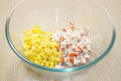 В миску нарезать кубиками крабовые палочки, добавить консервированную кукурузу.