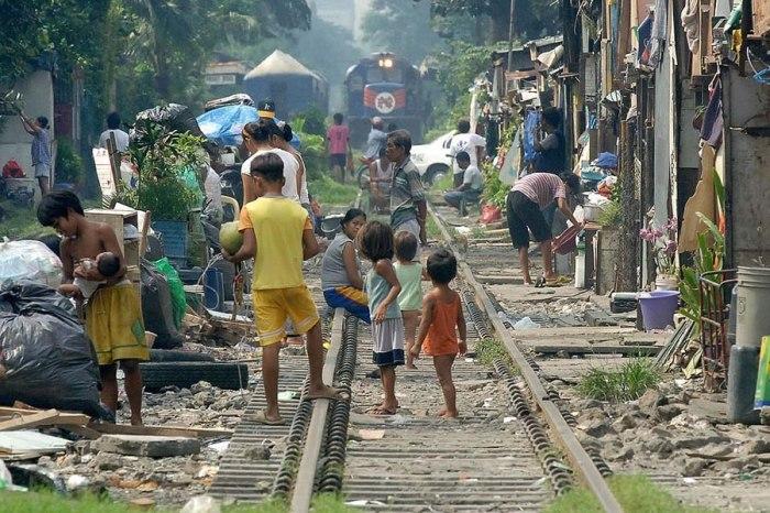 Филиппинские трущобы, прямо вдоль железной дороги, где буквально в метре от железнодорожных путей играют маленькие дети.