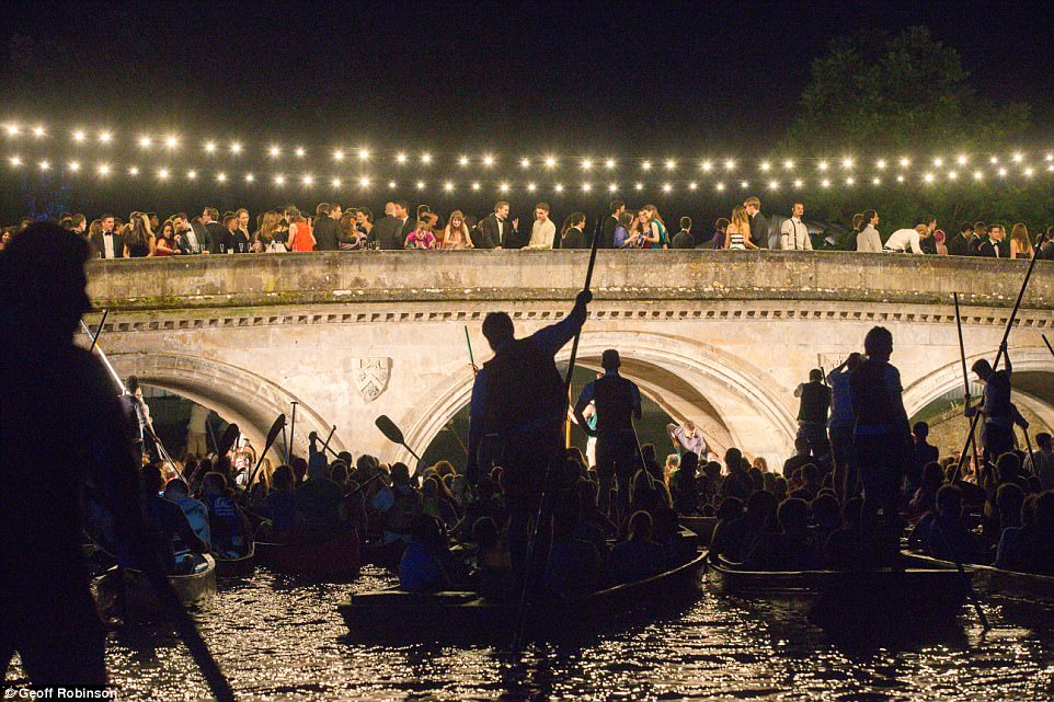Punters look on as students dressed in their finery chat and enjoy drinks on a bridge overlooking the River Cam