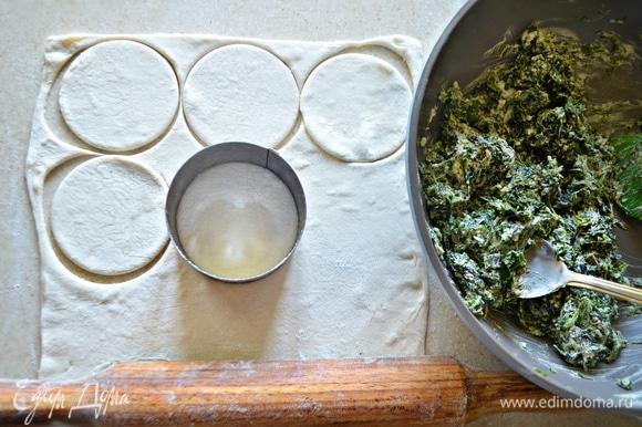 Тесто разморозьте при комнатной температуре и раскатайте на посыпанной мукой поверхности. С помощью кулинарного кольца вырежьте небольшие круги. Из 1 пласта теста получилось 9 шт. Остатки теста соберите в шар и снова раскатайте. Из всего теста получается порядка 27 заготовок для пирожков.