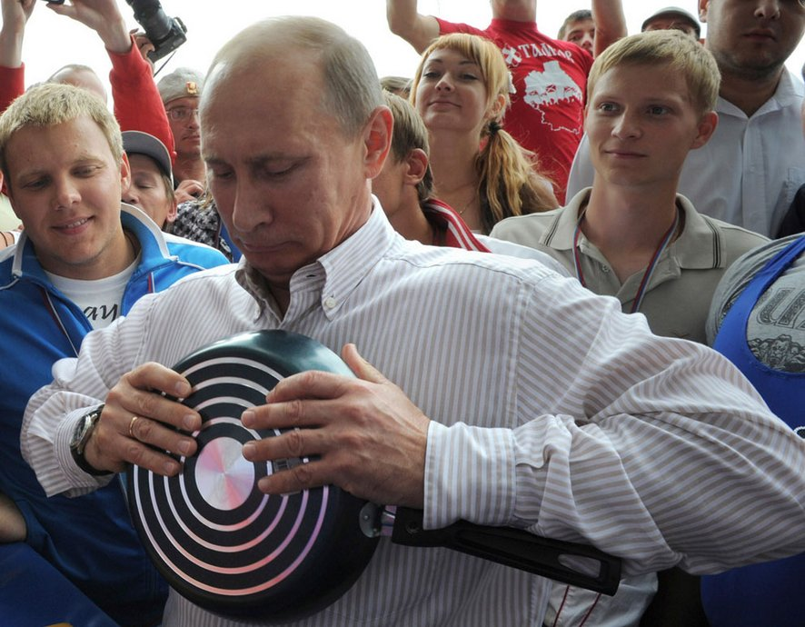 "The Russian president is trying to bend a frying pan hands.  Summer camp organization ""Nashi"", 400 km north of Moscow, August 1, 2011."