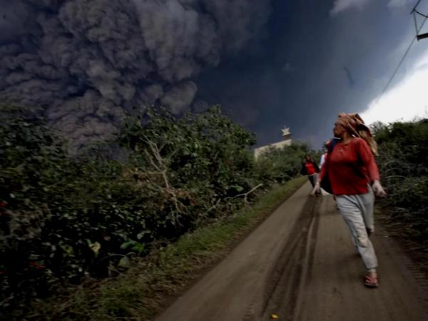 Люди бегут от извержения вулкана