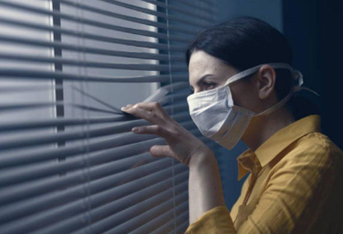 женщина в маске смотрит в окно