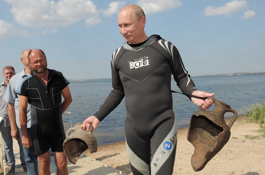Russian President holds two discoveries he made while diving near the archaeological site of the Taman Peninsula on 10 August 2011.