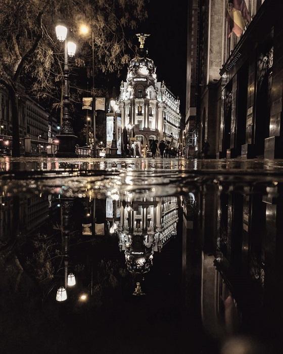 Здание Метрополис - символ испанской столицы в отражении луж.