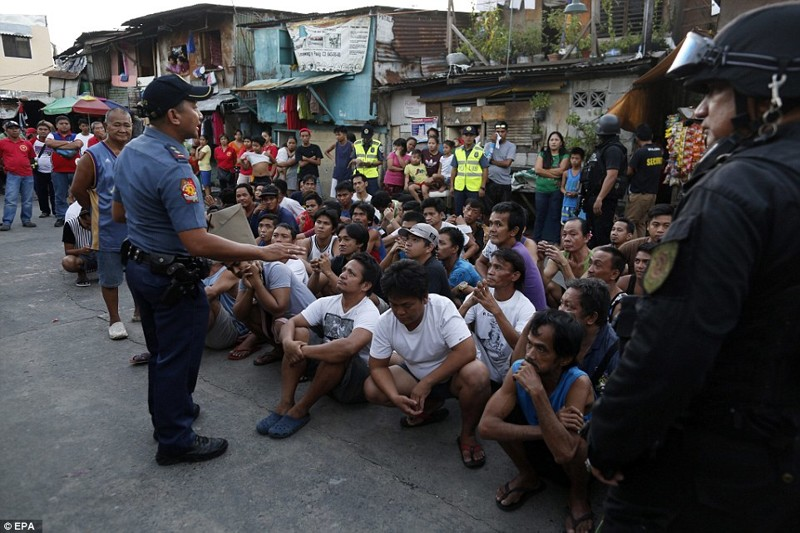 Жители города Pasig недалеко от Манилы сидят на земле, а филиппинский полицейский разговаривает с ними о наркотиках   дутерте, филиппины против наркотиков