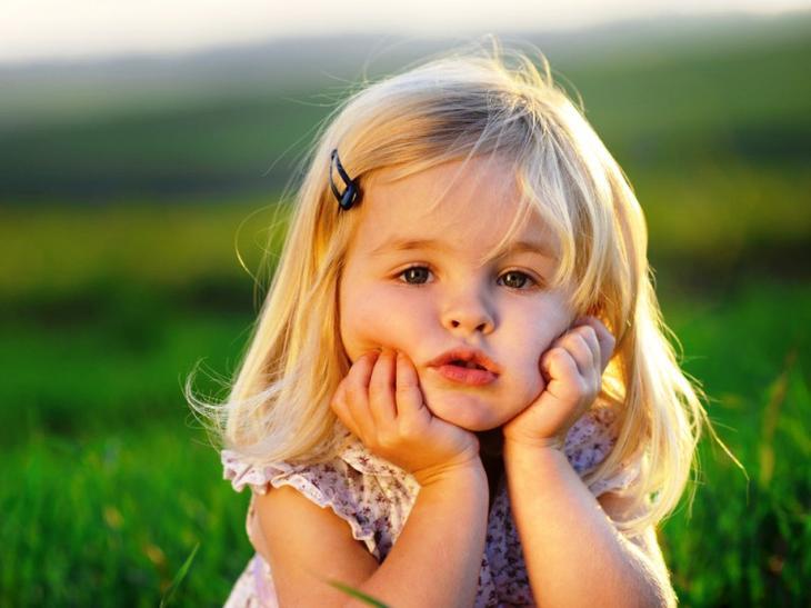 задумчивая девочка принимает солнечные ванны после нанесения лосьона с календулой