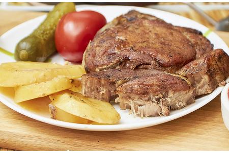 Фото к рецепту: Свиная корейка на косточке с картофелем в духовке