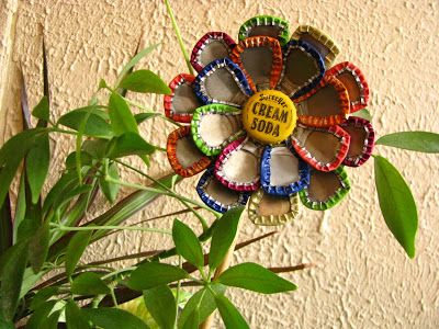 DIY Bottle Cap Flower Garden Art Stake It takes a little trial an error but all you do is take heavy duty pliers and smash the bottle caps into petal shapes and then epoxy or use a super glue rated for metal and attach to a can top in at least two circular rows. Then glue a stick to the back after it's dried 24 hrs. Easy once you get the hang of smashing bottle caps :):