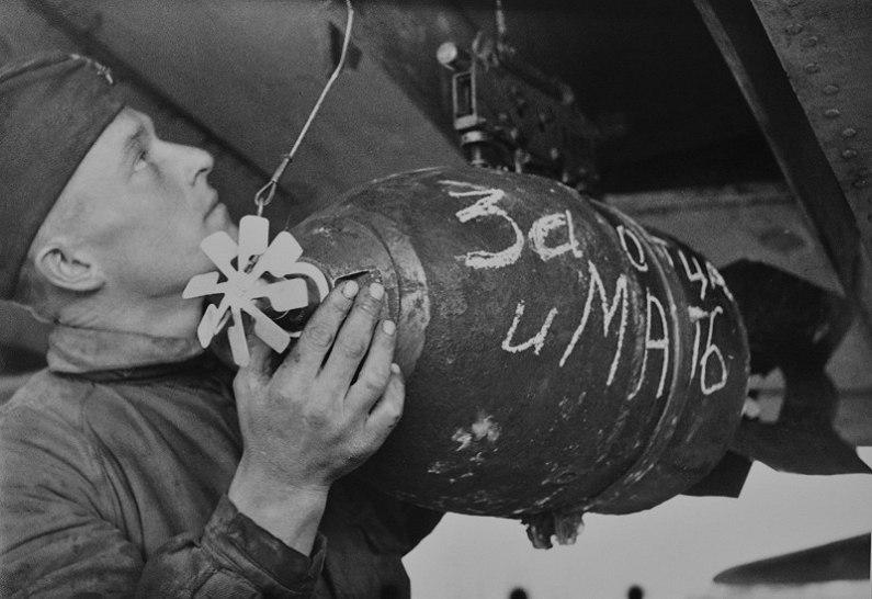 Советский боец-авиатехник закрепляет снаряды самолету дальней авиации.  1944-й