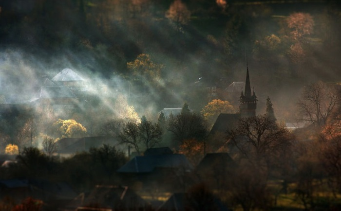 Потоки солнечного света пытаются пробиться сквозь облака и залить местность светом.