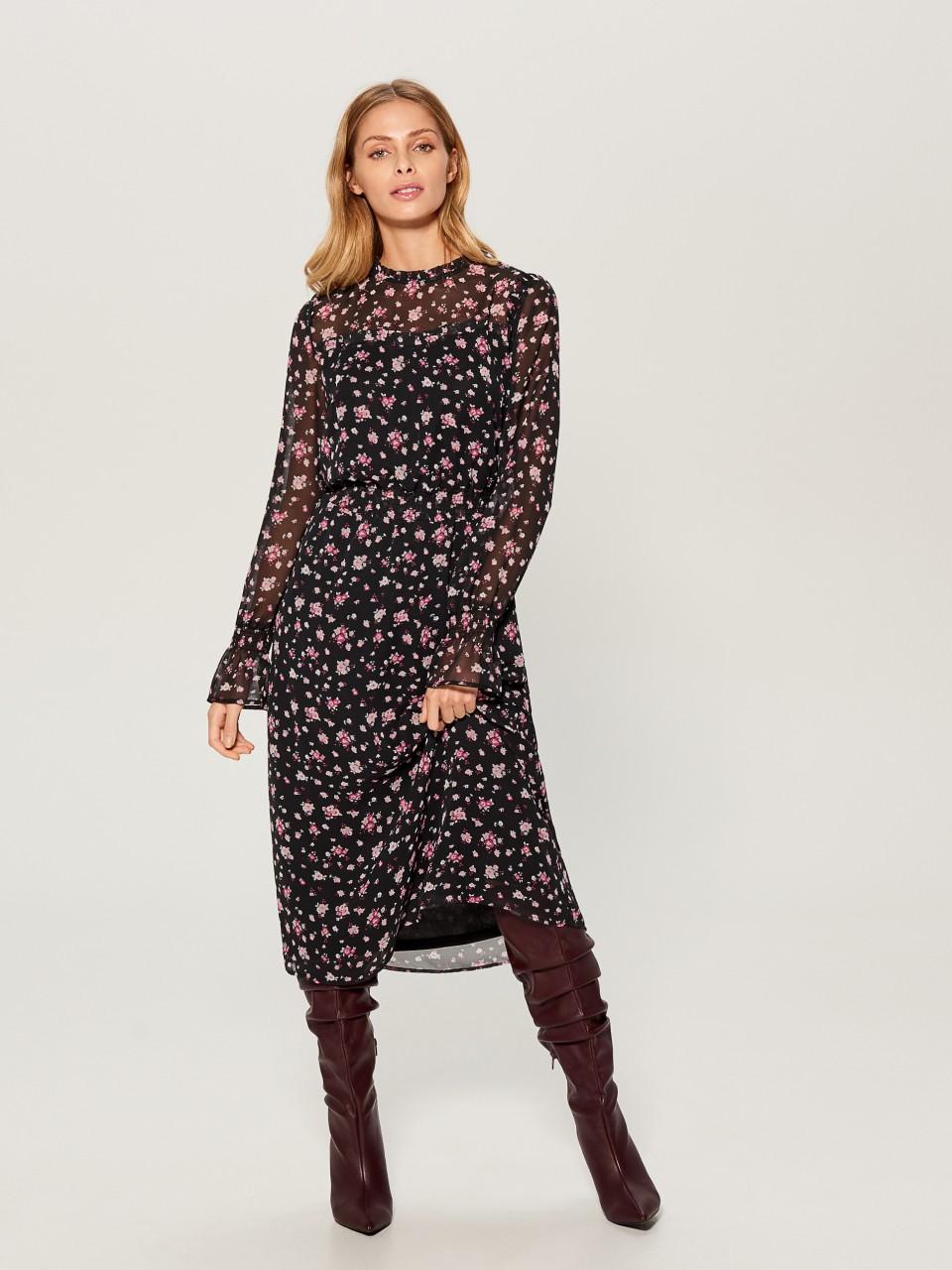 Девушка в платье с цветочным принтом и сапогах