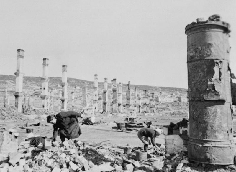 Женщины ищут уцелевшие вещи среди развалин после немецких бомбардировок Мурманска. Видны уцелевшие после пожаров печные трубы домов.