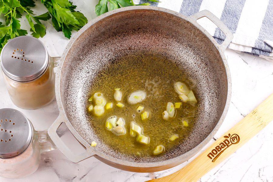 Растопите в казане или кастрюле с антипригарочным дном сливочное масло. Нарежьте очищенный репчатый лук и обжарьте его в масле примерно 2-3 минуты до румяности.