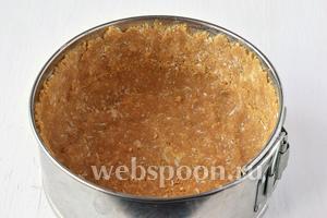 Форму диаметром 15 см выложить кулинарной бумагой. Смазать её маслом. Выложить массой из печенья дно и стенки формы, хорошо её прижимая.