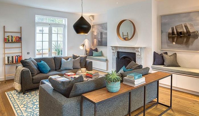 Деревянный стол дополняет общий интерьер комнаты для отдыха, которую дополняют и украшают серые диваны.
