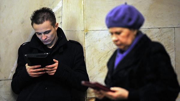 Пассажиры с портативными устройствами на одной из станций Кольцевой линии московского метрополитена