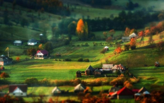 Живописная равнина с многочисленными постройками, утопающая в зелени трав.