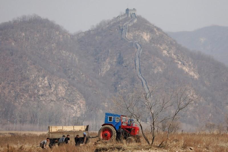3. Северокорейские фермеры работают в поле на границе, 2 апреля 2017. (Фото Damir Sagolj | Reuters): Тоталитаризм, гранциа, китай, севераня корея