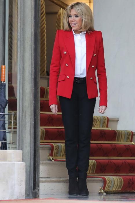 Брижит Макрон в черных брюках и красном жакете.