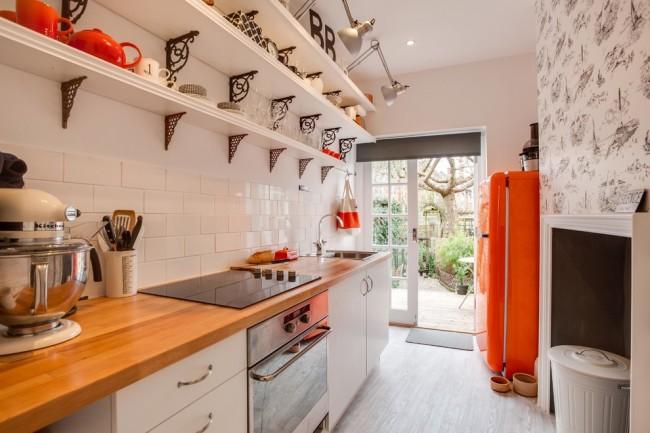 Открытые полочки с различными предметами декора выступают как украшение кухни