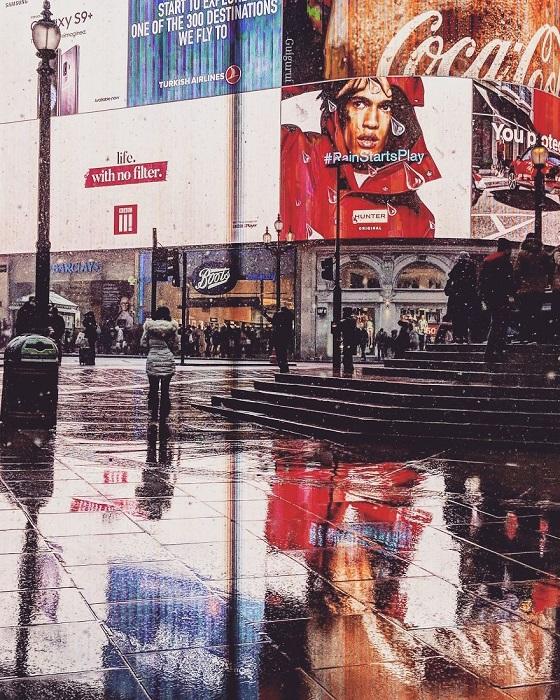 Поразительное отражение многолюдной улицы Лондона на мокром тротуаре.