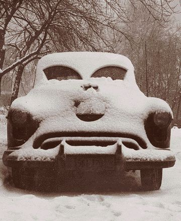 "SNOW IN APRIL MAKES ME CRANKY:   ""A snow-covered car looks unhappy with its plight after a 1952 storm."""