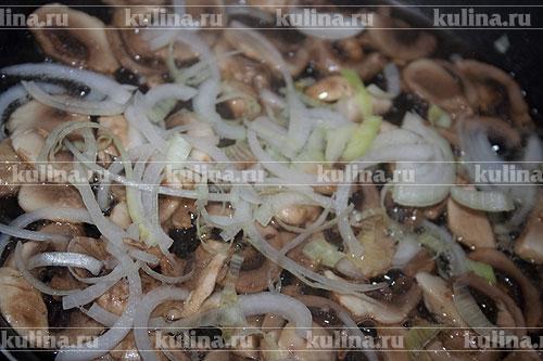 Через несколько минут добавить в сковороду нарезанный лук и обжаривать вместе с грибами до готовности.