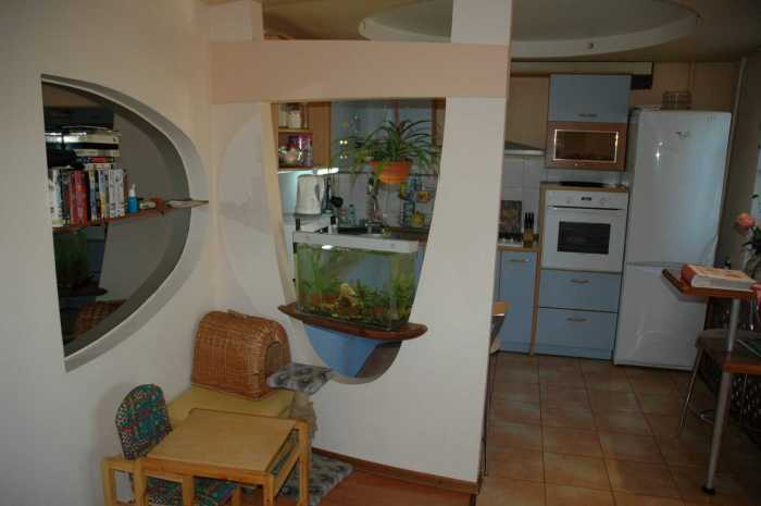 Оригинальная перегородка между кухней и гостиной прекрасно разделяет одно пространство две удобные и комфортные зоны.