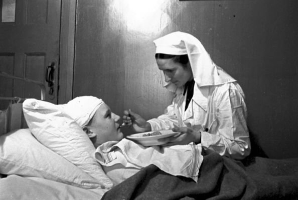 Медсестра Козлова А. кормит раненого майора Ногина В. в госпитале № 2-386.