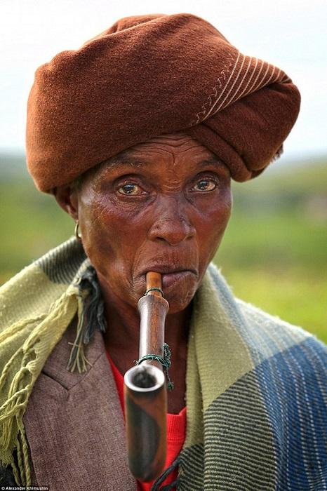 Пожилая представительница африканского народа Коса с огромной курительной трубкой.