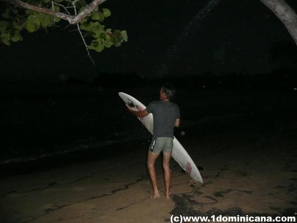 Серфер досочку моет после дня тренировок перед соревнованием
