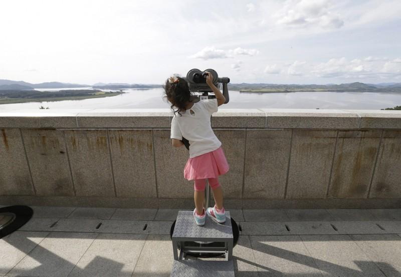 8. Южнокорейская девочка рассматривает северокорейскую территорию. (Фото Ahn Young-joon): Тоталитаризм, гранциа, китай, севераня корея